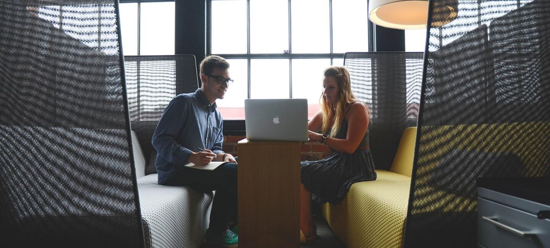 Dwóch młodych ludzi - mężczyzna i kobieta - siedzących na kanapach naprzeciwko siebie. Między nimi stolik oraz laptop, w który oboje się wpatrują.