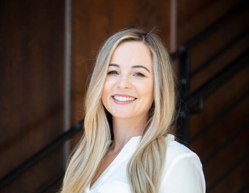 A headshot of Courtney Jones, CEO and founder of the ClearTheList Foundation and #ClearTheList, smiling against a black background.