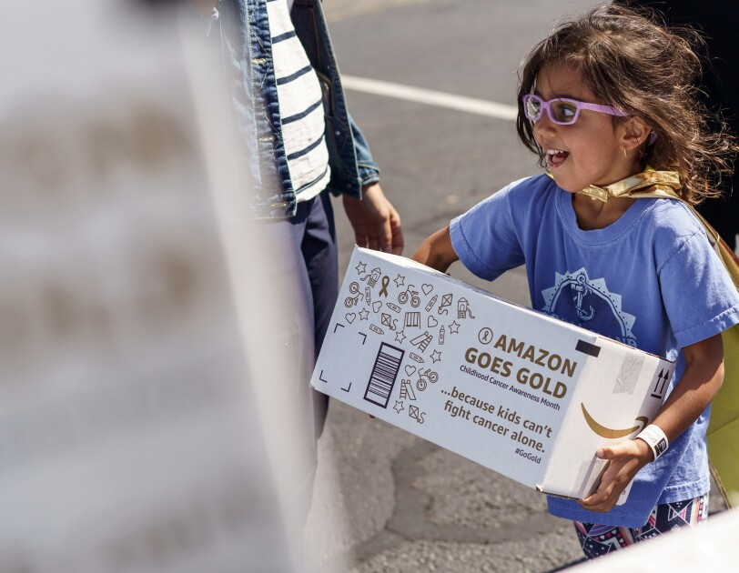 A child wearing pink glasses and a gold cape carries an Amazon Goes Gold box.