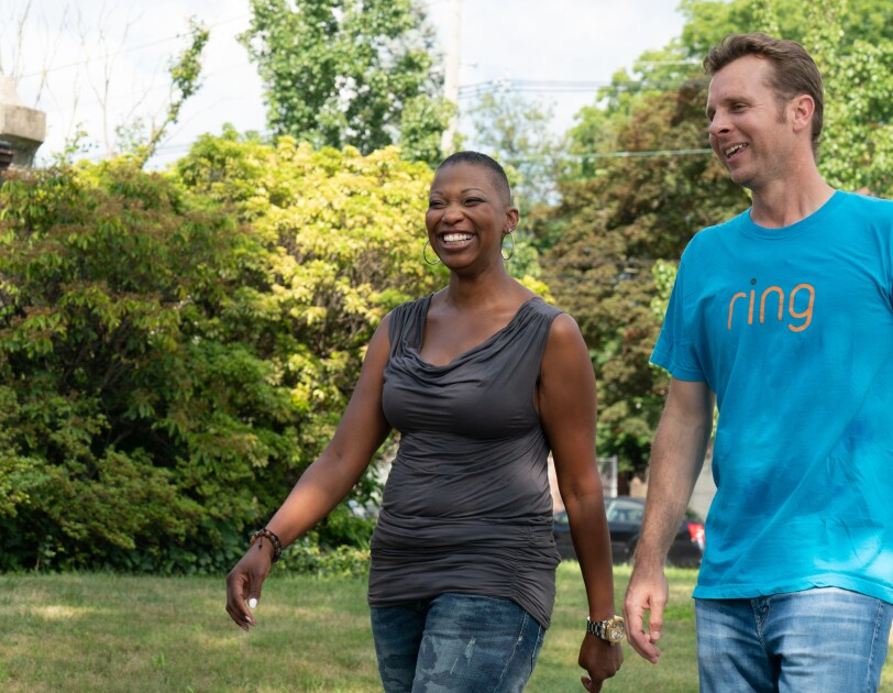 A Ring team member in blue t-shirts that have Ring on them with a female resident of Newark, New Jersey, who is wearing blue jeans and a grey tank top.
