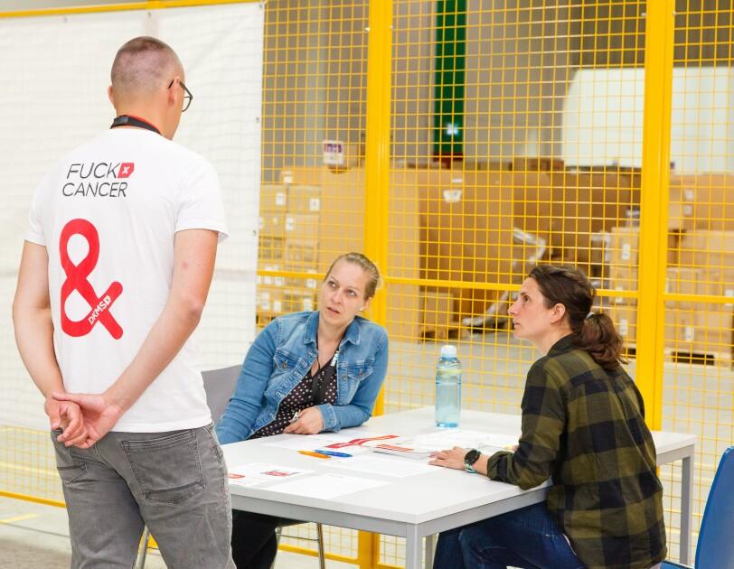 """Ein Mann in Rückenansicht trägt ein T-Shirt mit der Aufschrift """"Fuck Cancer"""", er steht in einem Logistikzentrum, vor ihm ein Tisch, an dem 2 Frauen sitzen"""