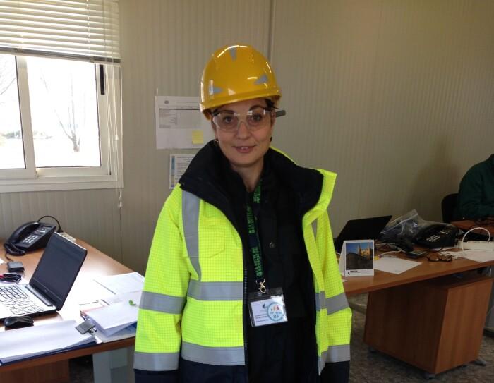 Donna in piedi in un ufficio in un centro operativo Amazon. Indossa un caschetto protettivo giallo