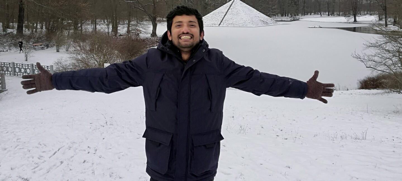 Ein junger Mann mit ausgebreiteten Armen im beschneiten Park