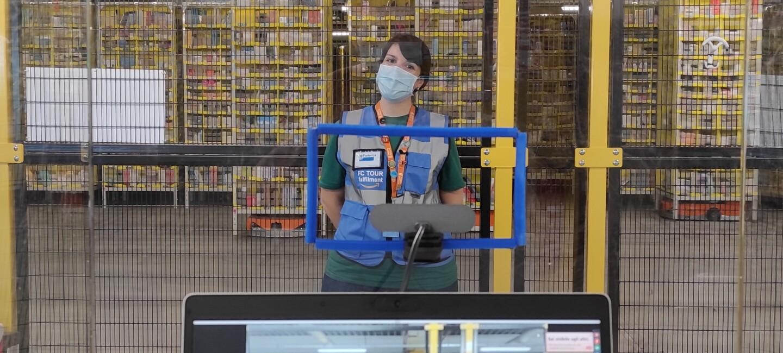 In primo piano un tablet con la fotocamera accesa. Sullo schermo si vede una ragazza all'interno di un magazzino Amazon. La ragazza è posizionata di fronte al tablet, indossa una mascherina chirurgica e un giubbino catarinfrangente blu con la scritta FC Tour Ambassador. Alle sue spalle, una griglia la separa dall'area robotica del magazzino, in cui si vedono le colonne di prodotti trasportate dai robottini.