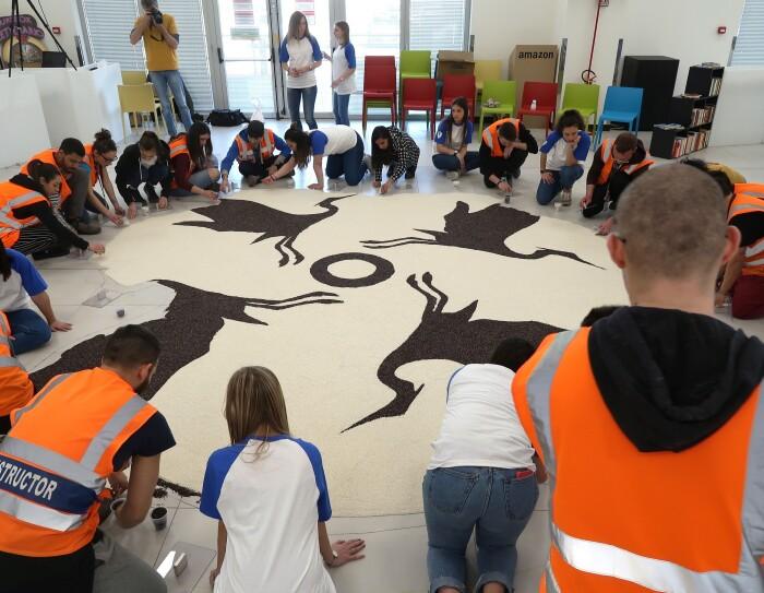 gruppo di dipendenti Amazon del centro di distribuzione di Vercelli seduto in terra attorno ad un Mandala in composizione