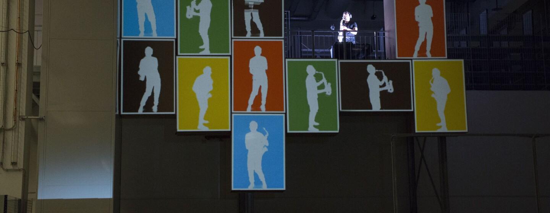 Video mapping realizzato al Centro di Distribuzione Amazon di Piacenza. Il disegno ricrea le sagome di un sassofonista in diverse posizioni, sullo sfondo di cubi colorati.