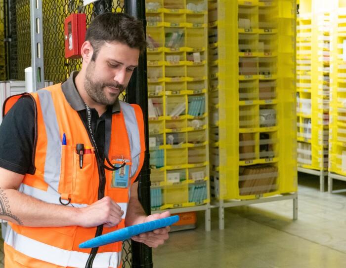 Raúl Cruz, técnico senior de mantenimiento en robótica, con el Kindle controlandos los robots. En primer plano está Raúl, con el pelo negro y barba, vestido con una camiseta negra y el chaleco naraja. En la mano está manipulando un Kindle con una funda azul. De fondo tiene las pods, estanterías que trasladan los robots.