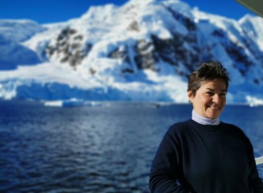 Christiana Figueres en la Antártida con un glaciar de fondo. Ella va vestida con un jersei azul y debajo un polo de cuello alto. EL fondo se ve el mar azul, una montña nevada y un glaciar.