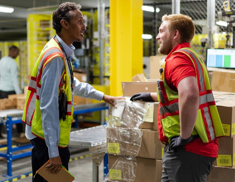 Two men talk in a warehouse setting.