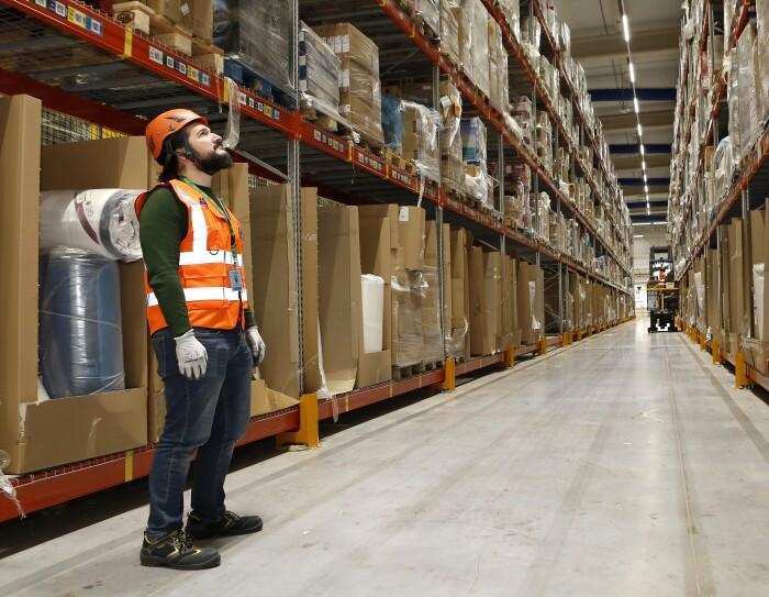 Sergio Amador lidera el equipo de Health & Safety de los centros de Amazon Operaciones en España. Va con casco naranja, chaleco y guantes. Observa las estanterías llenas de cajas.