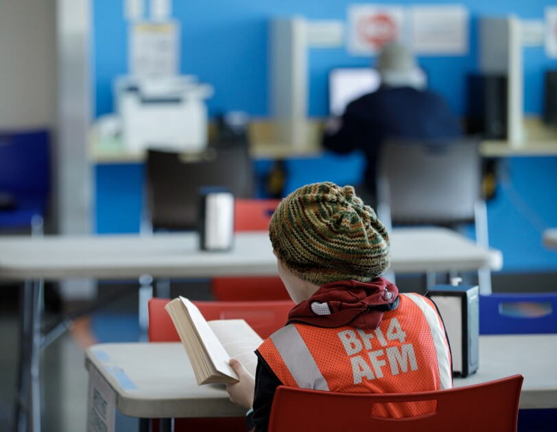 A person in a warm hat and safety vest sits at a table and reads a book.