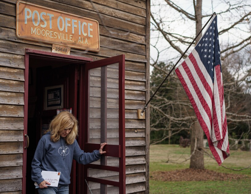 """A woman exits a wooden building with a sign that says """"Post Office"""" and """"Mooresville, Alabama."""""""