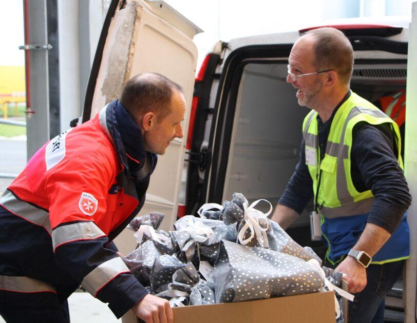 Ein Logistikmitarbeiter belädt den Christmas Van zusammen mit einem Mitarbeiter der Malteser/Frankenthaler Tafel.
