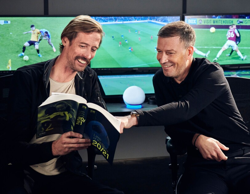 Peter Crouch (left) and Mark Clattenburg (right) reading through a football rule book in front of screens showing football games. On a table between them is the Amazon Echo Dot.