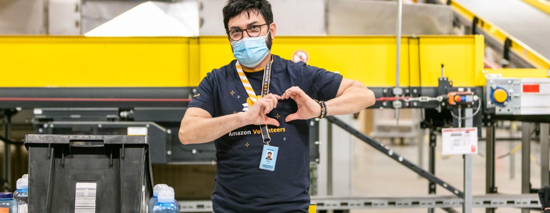 Ein Amazon Mitarbeiter mit Maske formt mit den Händen ein Herz. Auf dem T-Shirt liest man Amazon Volunteers.
