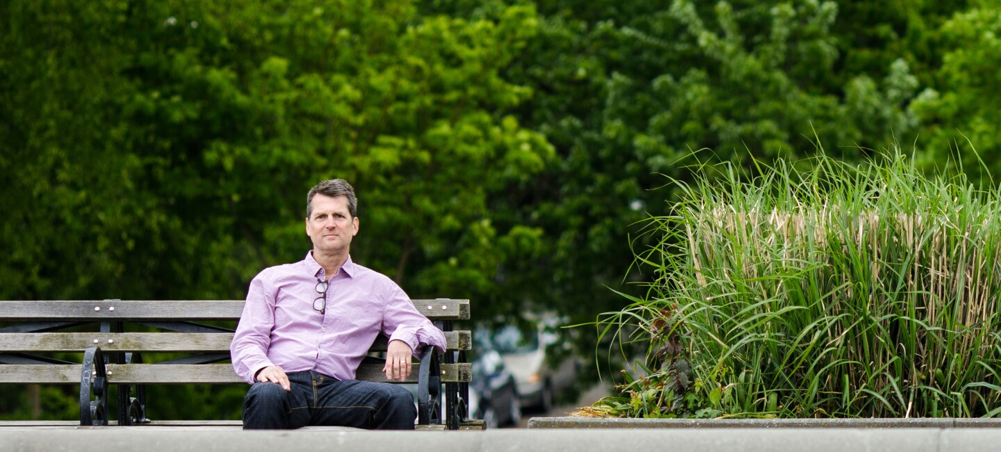Amazon employee Neal Thompson sits on a bench. He wears a purple button-down shirt. A pair of glasses hang from his open color.