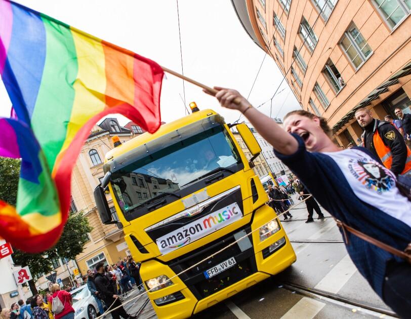 """Ein Lkw mit der Aufschrift """"Amazon Music"""" und feiernde Menschen beim CSD 2019"""