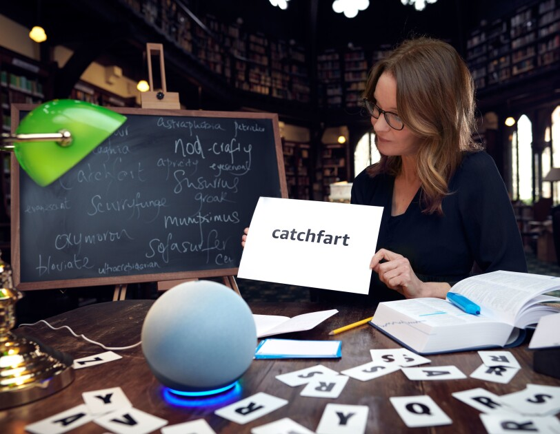 """Susie Dent sitting at a library table next to a whiteboard holding a card that says the word """"catchfart"""". On the table in front of Suzie there is an Amazon Echo and lots of letter cards."""