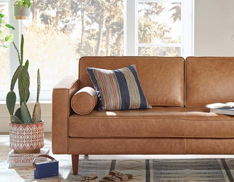 A geometric planter holds a large cactus, and sits atop several coffee table books. Next to it is a leather midcentury sofa, topped with a striped pillow. The sofa and planter both sit on a faded geometric rug.
