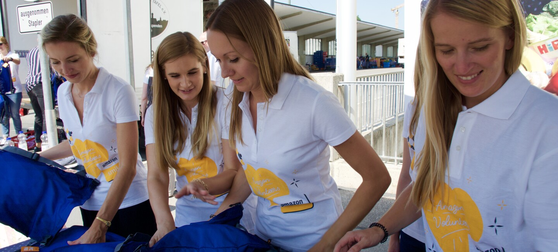 4 Helferinnen von Amazon verteilen blaue Schulbeutel.
