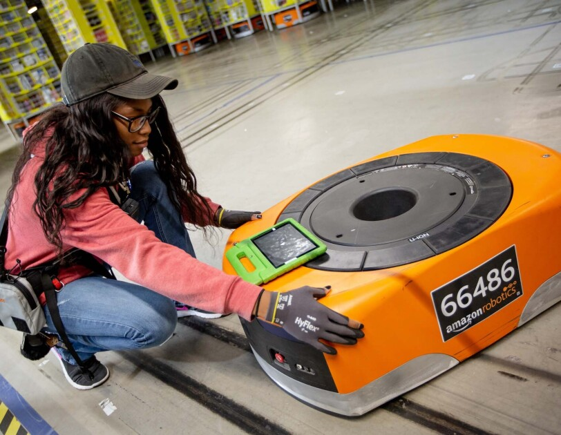 A woman kneels next to a robot, while also working on a tablet, at a Columbus, Ohio fulfillment center, CMH1