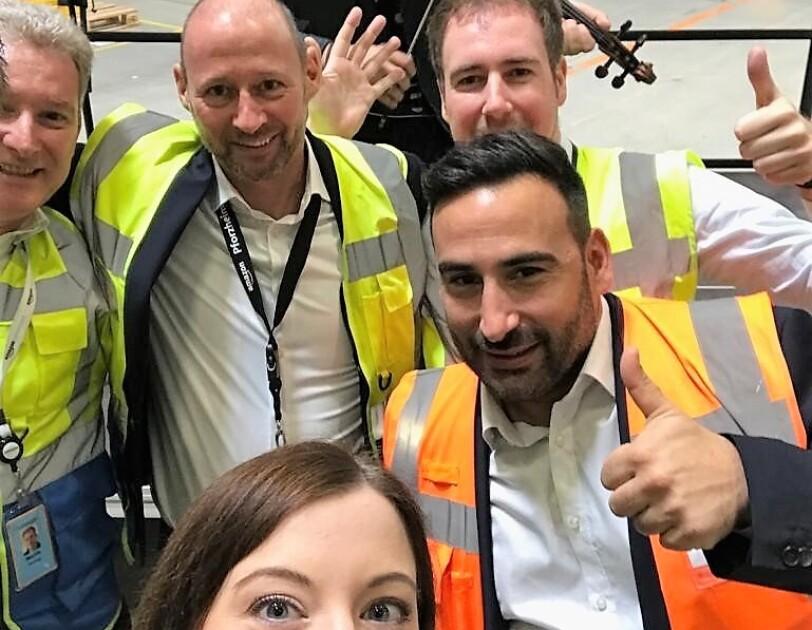 Selfie mit fünf Amazon Mitarbeitern, davon eine junge Frau, und dem jungen Geiger