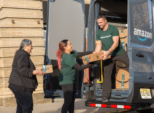 A man standing in an Amazon delivery van passes packages to two women standing on the ground.