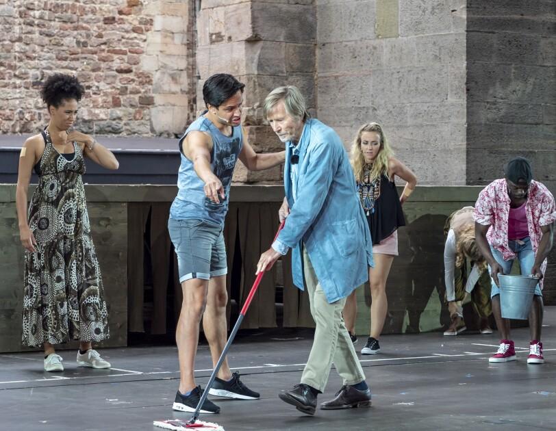 Horst Janson als Hausmeister ist auf der Bühne mit weiteren Schauspielern zu sehen