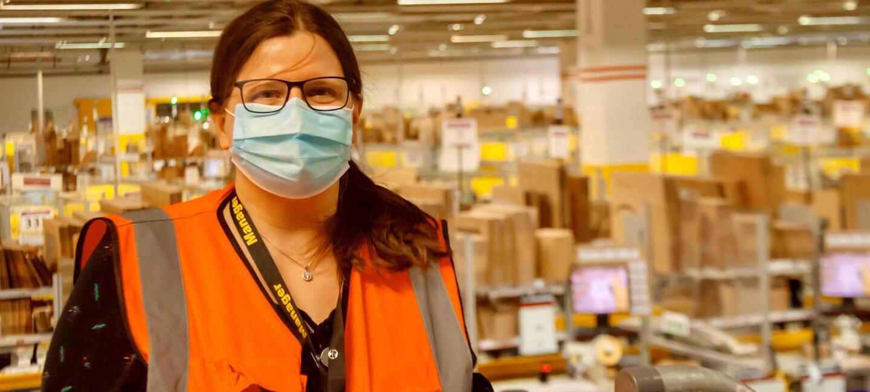 Eine Frau mit Brille, Mundschutz und braunen langen Haaren steht in einer Logistikhalle.