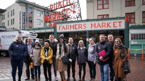 A group of Amazon employees from the 'I Found The Right Place' programme standing outside of a farmers market.
