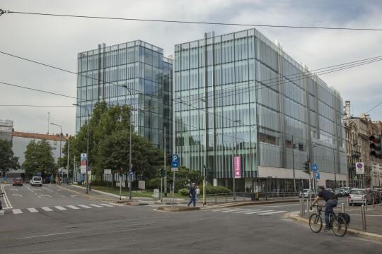 Due edifici in vetro visti dall'altro lato della strada. Gli edifici sono uguali e speculari. Un uomo in bicicletta a destra dell'immagine sta per attraversare la strada, mentre un pedone occupa l'incrocio.