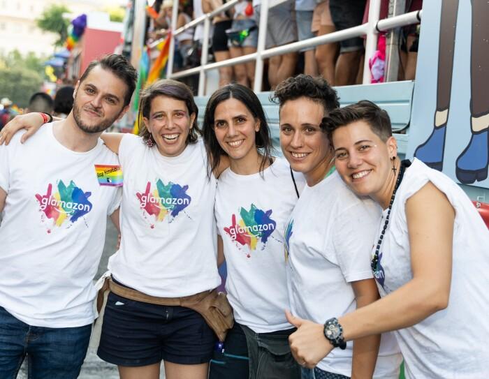 Simone Fortunini, Coia Pons, Eva Ahijado, María García y Susana Torres delante la carroza de glamazon del desfile del Día del orgullo LGTBI. Los cinco lucen la camiseta de glamazon y miran a cámara sonriendo.