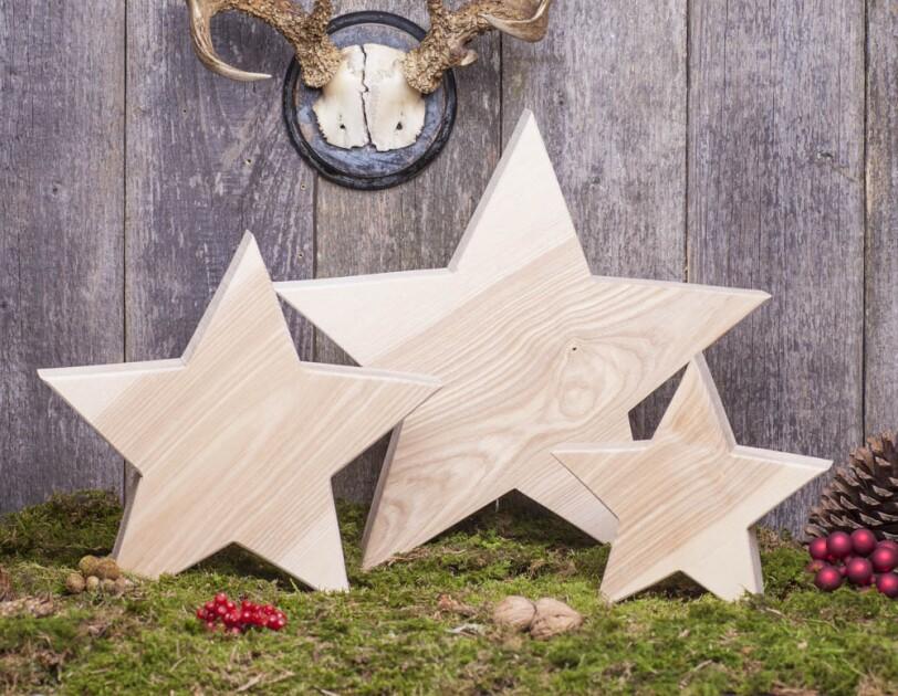 Drei Holzsterne stehen vor einer Holzwand. Sie habe unterschiedliche Größen und stehen auf einem Moosteppich.