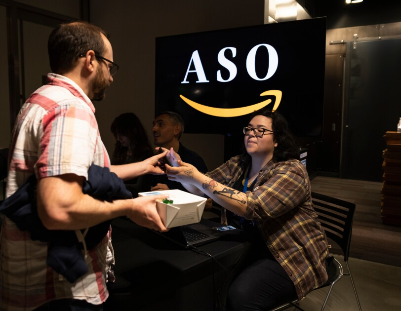 "A woman helps a man check in at an event. A sign in the background shows the Amazon smile logo and the letters ""ASO."""
