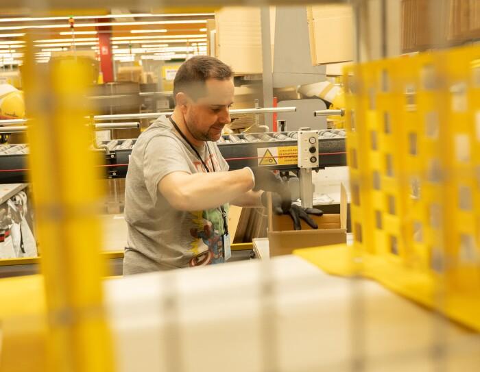 En primer plano hay una estantería amarilla y en segundo plano un asociado empaquetando un pedido. De fondo se puede ver la cinta transportadora. El asociado va en manga corta y lleva guantes negros.