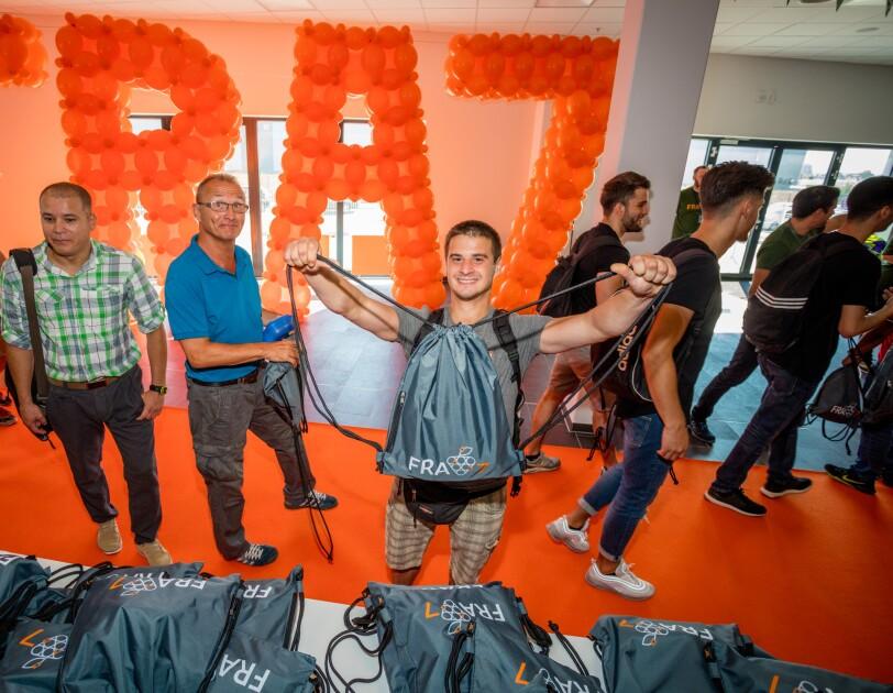 """Neue Mitarbeiter beim Betreten des Logistikzentrum in Frankenthal. Sie halten einen Willkommensbeutel in der Hand. Im Hintergrund ist ein rotes """"FRA7"""" Logo aus Luftballons zu sehen."""