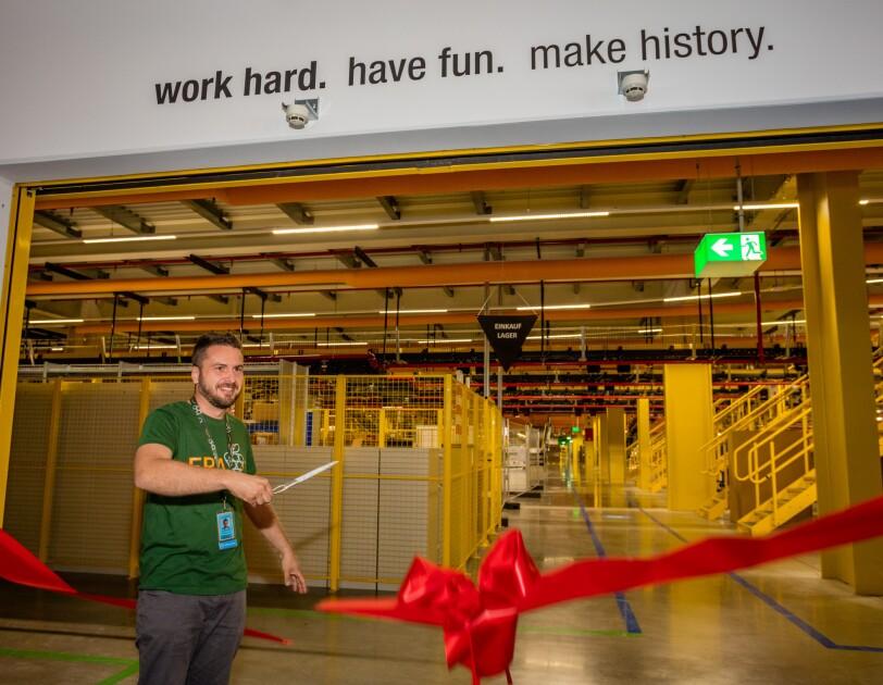 """Ein großes, geöffnetes Eingangstor zeigt den Blick in eine Lagerhalle: Man sieht gelbe Treppen und einen gelb eingezäunten Regalbereich. Links im Bild ist der Standortleiter zu sehen. Er trägt ein grünes T-Shirt mit Aufschrift """"FRA7"""" und hält eine Schere in der Hand. Er ist im Begriff, ein riesiges rotes Schleibenband, das am Eingangstor angebracht ist, zu zerschneiden."""