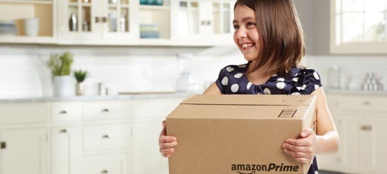 Bambina con un vestito blu a pois bianchi regge una scatola con il logo Amazon Prime, nella cucina della sua casa.