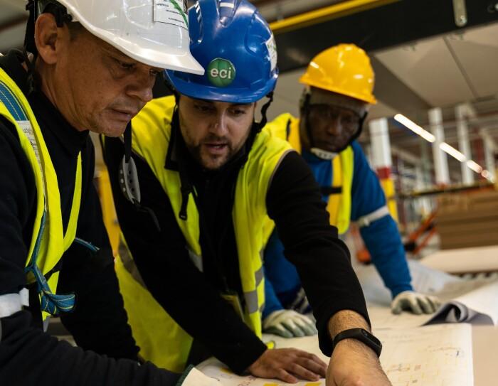 Aparecen tres personas trabajando con un plano.  Las tres llevan cascos; blanco, azul y amarillo y chalecos amarillos y están trabajando en un plano que está sobre una mesa. Se ven cinco manos, tres de ellas con guantes blancos.