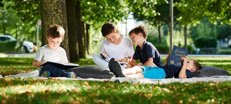 Kinder sitzen im Wald auf einer Picknickdecke und lesen