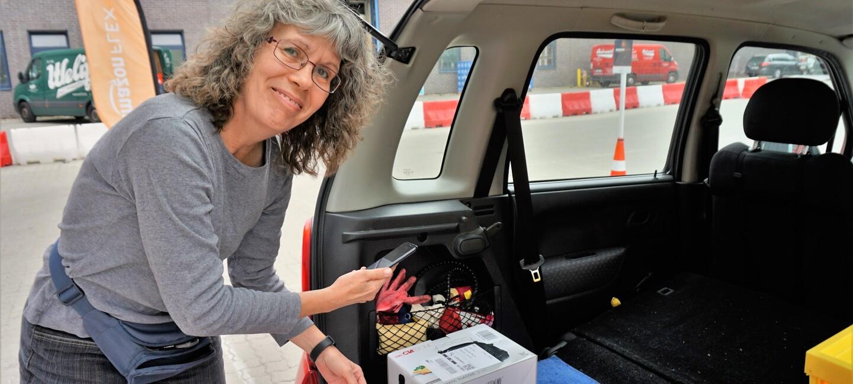 Links im Bild: die Flex Fahrerin Iris Paul. Sie steht vor einem geöffneten Kofferraum, in dem ein Paket zu sehen ist.