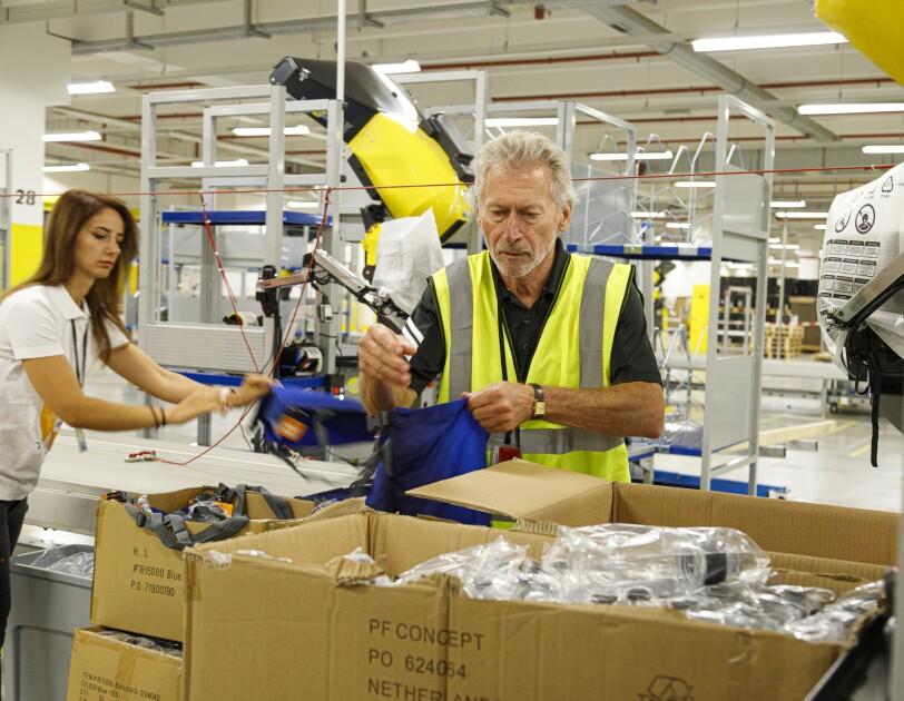 Ex-Fußballprofi Paul Breitner packte im Amazon Logistikzentrum Graben mit an für benachteiligte Schüler.jpg