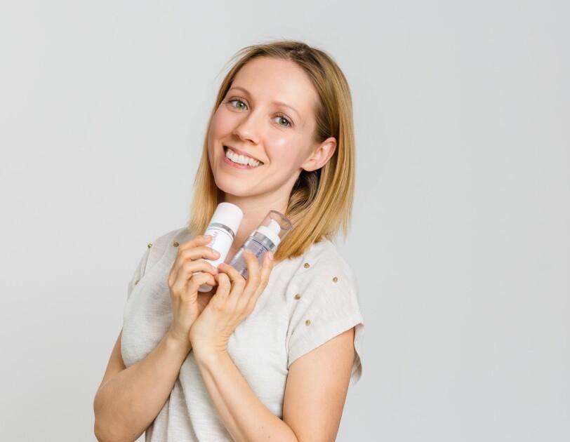 Eine Frau mit blonden Haaren und einem weißen T-shirt lächelt in die Kamera. In ihren Händen hält sie zwei Kosmetikflaschen.