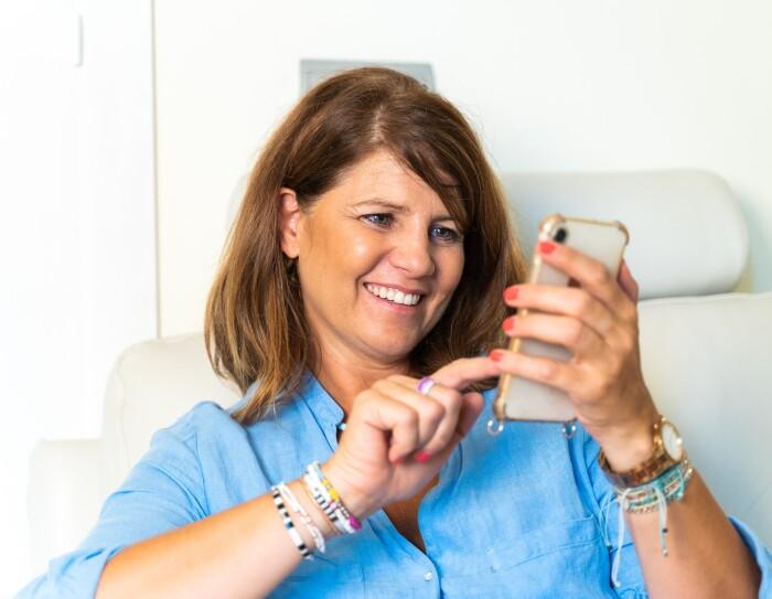 Gloria lleva una camisa de hilo, un collar azul y blanco, el pelo por el hombro suelto. Está sentada en un sofá blanco. En la mano lleva un teléfono móvil. Las uñas de las manos de color rojo, un reloj en la mano izquierda y pulseras en las dos muñecas.