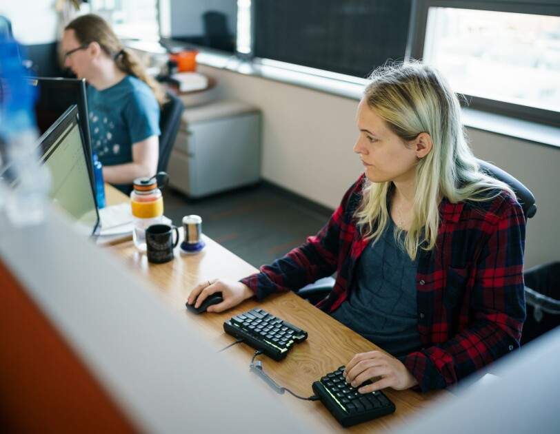 Danielle Skysdottir sits at her desk in a cubicle at Amazon's Seattle headquarters. She has blond hair and is wearing a T-shirt and flannel shirt. She's using a computer mouse with her right hand and typing on a split ergonomic keyboard with her left hand.