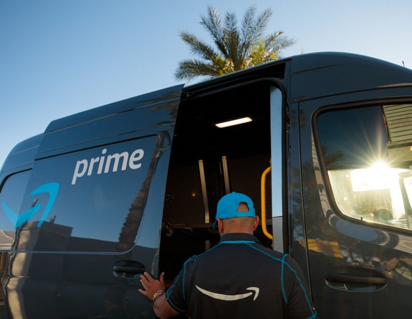 "A uniformed driver slides the door of a vehicle with word ""prime"" and the Amazon smile logo. A palm tree is in the background."