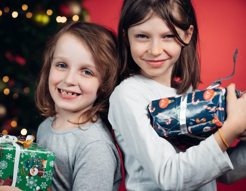 Zwei dunkelhaarige Mädchen lächeln in die Kamera. Beide tragen jeweils ein Geschenk in ihren Armen.