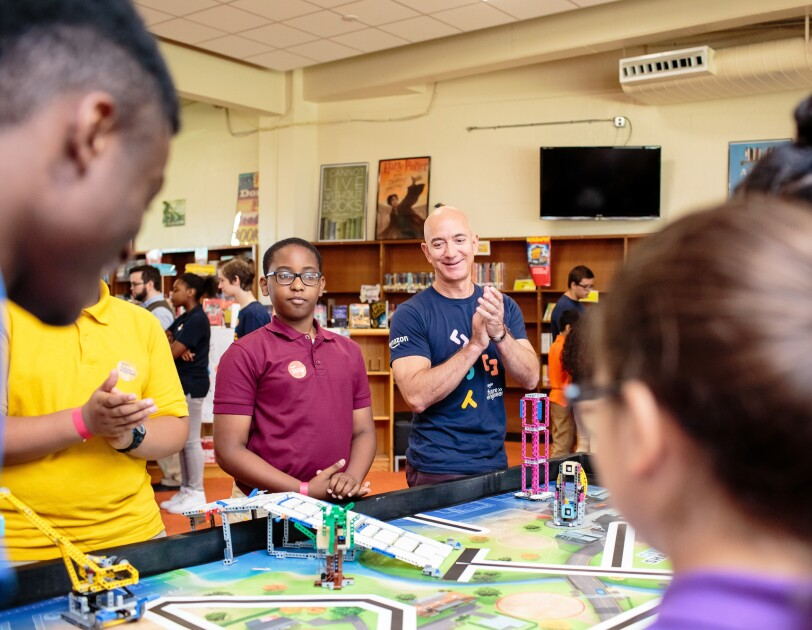Jeff Bezos and students of various ages gather around a tabletop decorated with roads. STEM toys are on the table.