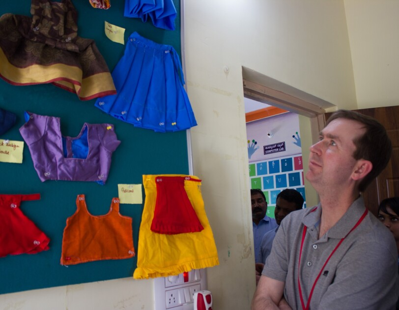 John Felton  looks at some clothes stitched by women at the Community Centres.