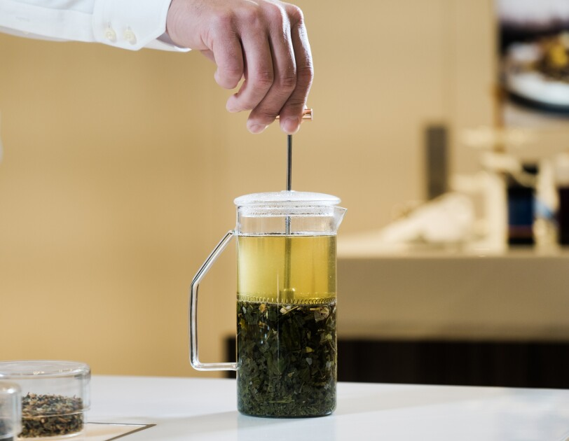 Tea steeps in a French press style pitcher. A person's hand is poised atop the plunger that is pressed down to isolate the tea leaves from the finished beverage.